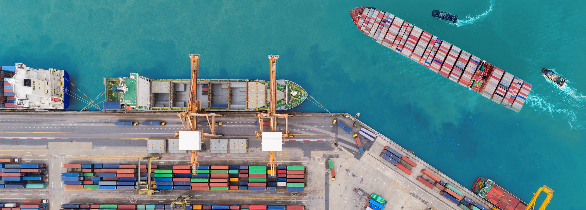 Aerial top view container ship at sea port and working crane bridge